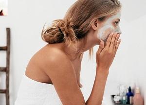 En kvinna applicerar sin fuktmask