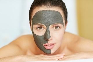 Tjej med en ansiktsmask av lera