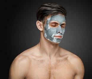 En kille med en lermask på ansiktet