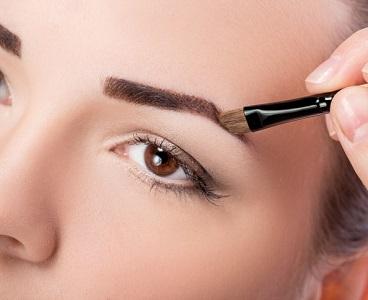 En kvinna fyller i sina ögonbryn