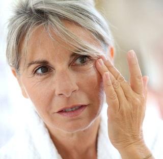 En äldre kvinna som använder concealer