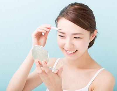 En kvinna som använder en ögonbrynskniv